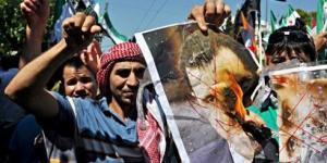 Protesters burn images of President Bashar al-Assad during the Arab Spring