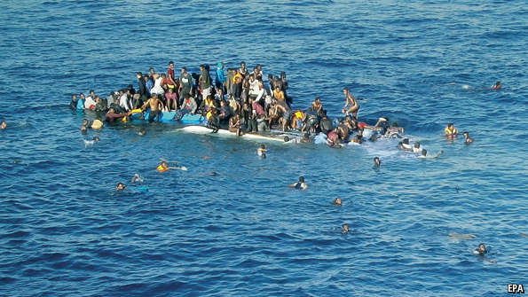 Asylum Seekers cling to their cap-sized boat. (Source: The Economist)