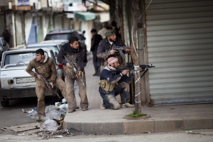 Syrian rebels take position during clashes with Syrian Army forces in Idlib, northern Syria. (photo credit: AP/Rodrigo Abd)