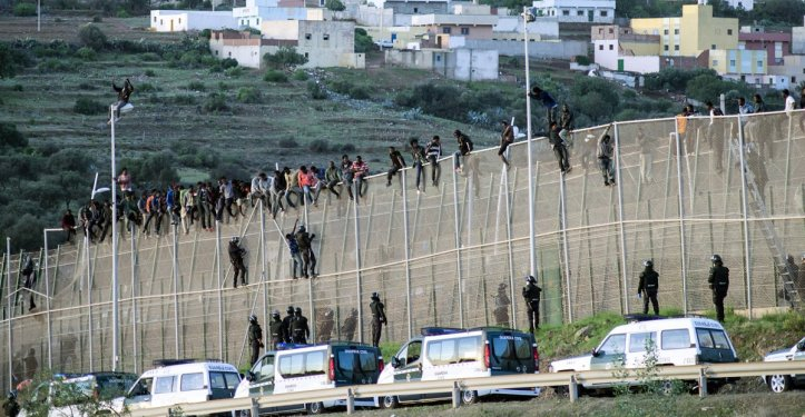 Desperate people attempt to scale the border fences in Algeria in their attempt to enter Western Europe
