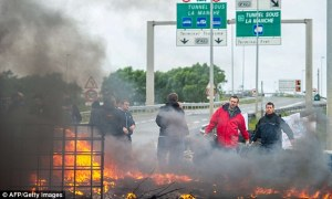 Asylum seekers burn tires as a make shift road block in Calais, as they attempt to cross the channel tunnel into the UK