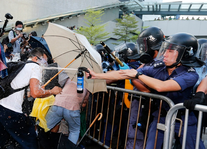 A riot policeman (R) uses pepper spray during clash with protesters, as tens of thousands of protesters block the main street to the financial Central district outside the government headquarters in Hong Kong, September 28, 2014. Source: Tyrone Slu/Reuters
