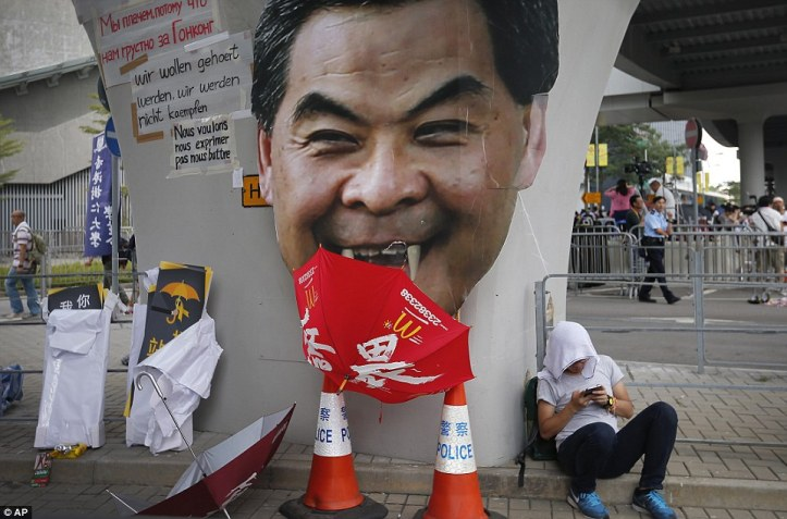 A student protester rests next to a defaced poster of Chief Executive Leung Photo:AP