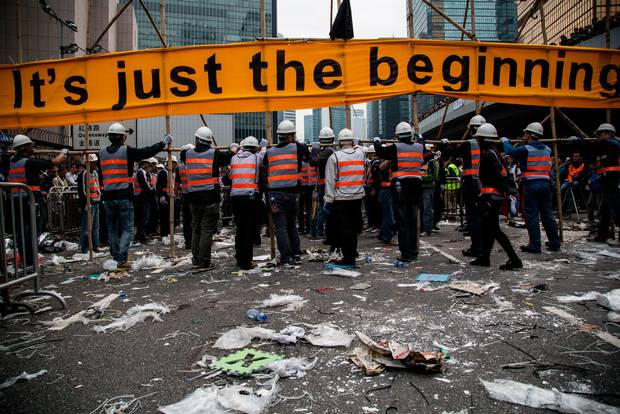 "Workers dismantle a barricade erected by pro-democracy protesters with a banner reading ""It's Just The Beginning"" near the Central Government Offices in the Admiralty district. (Lam Yik Fei/Bloomberg)"