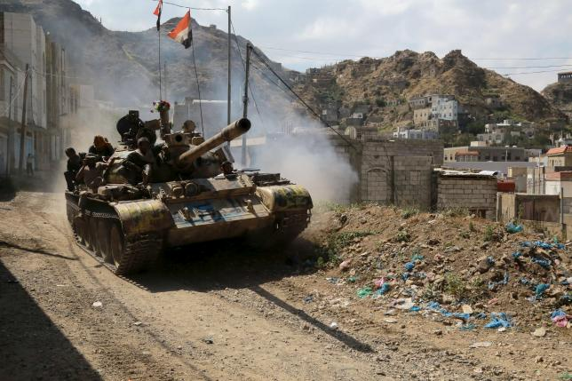 Soldiers loyal to Yemen's government ride atop a tank in the country's southwestern city of Taiz