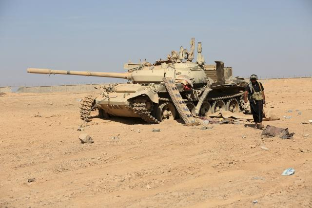 Tribesman loyal to Yemen's President Abd-Rabbu Mansour Hadi walks past a damaged tank at the Mass army barracks after the pro-Hadi forces took it from Houthi rebels in the country's northwestern province of Marib