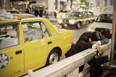 A man rests on his commute home. Image by Adrian Storey. Source: Japan Times
