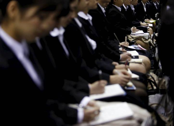Young prospective female employees take notes at a job fair. Source: Japan Times/Reuters.