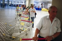 Customers wait in line at a state run supermarket. Image Credit: Jorge Silva/Reuters