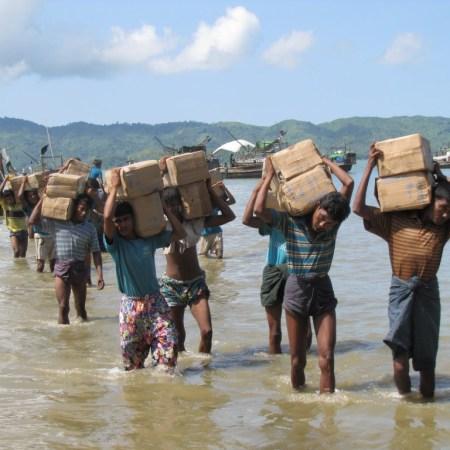 Rohingya refugees walk with their supplies