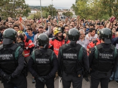 SANT JULIA DE RAMIS, SPAIN - OCTOBER 01: Police move back to their vans followed by members of the public after storming into polling station to confiscate ballot boxes and ballots where the President Carles Puigdemunt will vote later today on October 1, 2017 in Sant Julia de Ramis, Spain. More than five million elegible Catalan voters are estimated to visit 2,315 polling stations today for the Catalonia's referendum on independence from Spain. The Spanish government in Madrid has declared the vote illegal and undemocratic. (Photo by David Ramos/Getty Images)